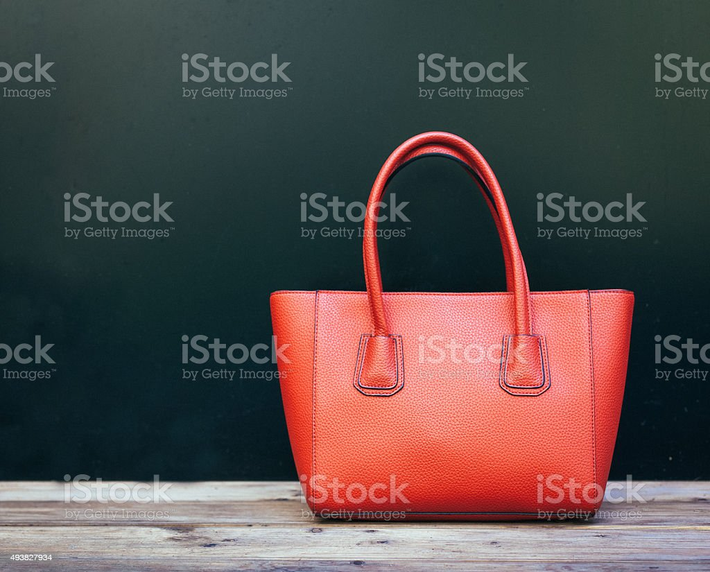 Fashionable beautiful big red handbag standing on a wooden floor stock photo