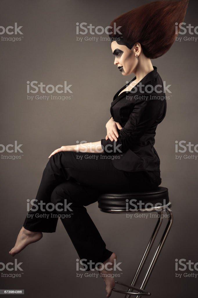 fashionable beautiful business woman sitting on bar stool with lush hair stock photo