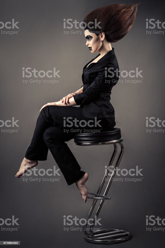 fashionable beautiful business woman sitting on bar stool with lush hair and dark make-up stock photo