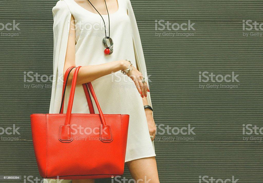 Fashionable beautiful red handbag on the arm of the girl stock photo