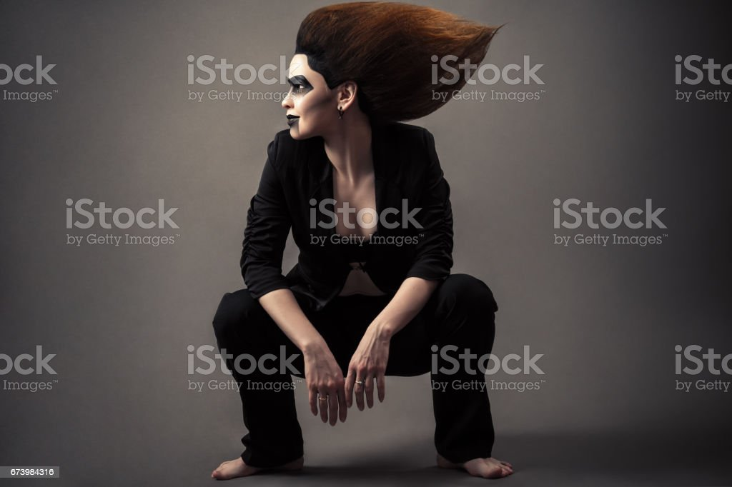 fashionable beautiful woman sitting on squat with lush hair and dark make-up stock photo