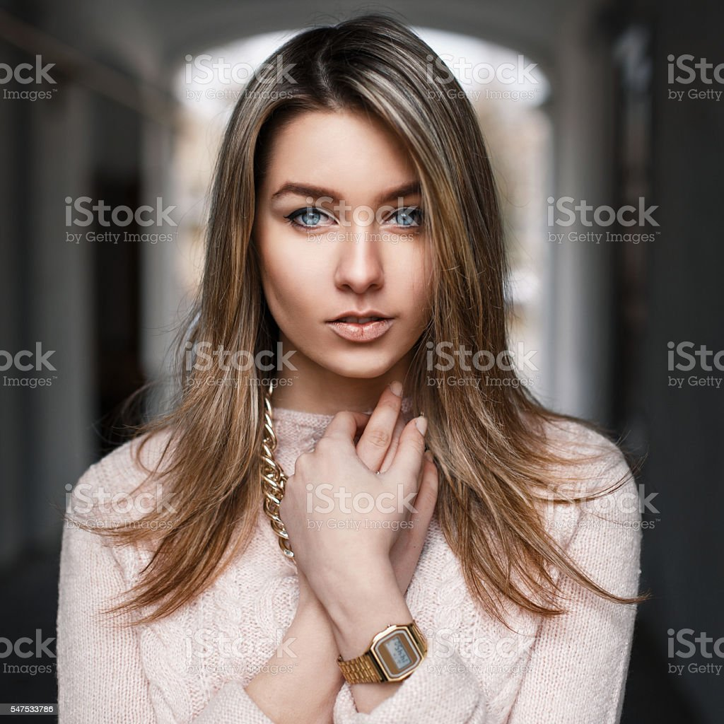 Fashionable beautiful young girl in a pink sweater stock photo