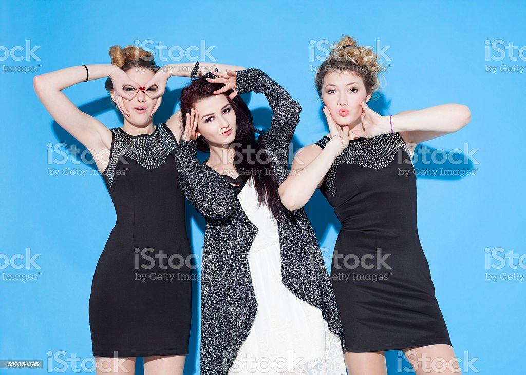 Fashionable beautiful young girlfriends standing together near a blue background. stock photo
