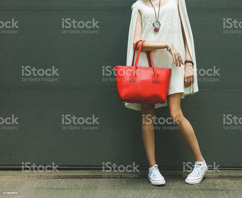 Fashionable big red handbag on the arm of the girl stock photo