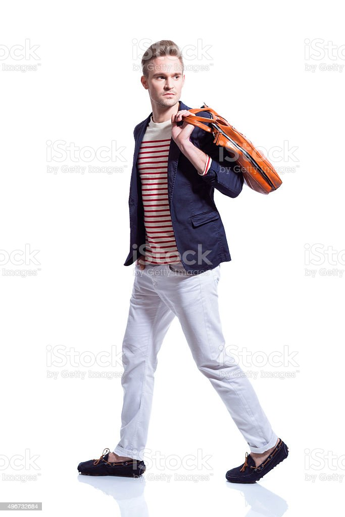 Fashionable blonde young man holding bag stock photo