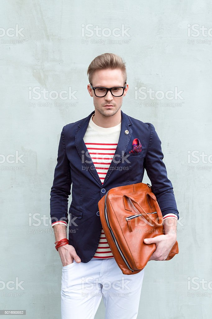Fashionable blonde young man holding leather bag stock photo