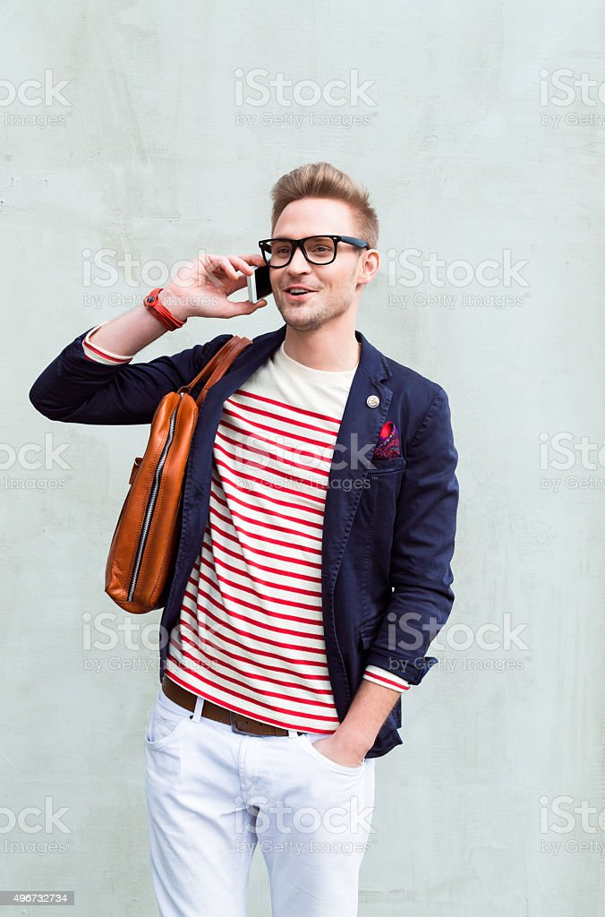 Fashionable blonde young man talking on cell phone stock photo