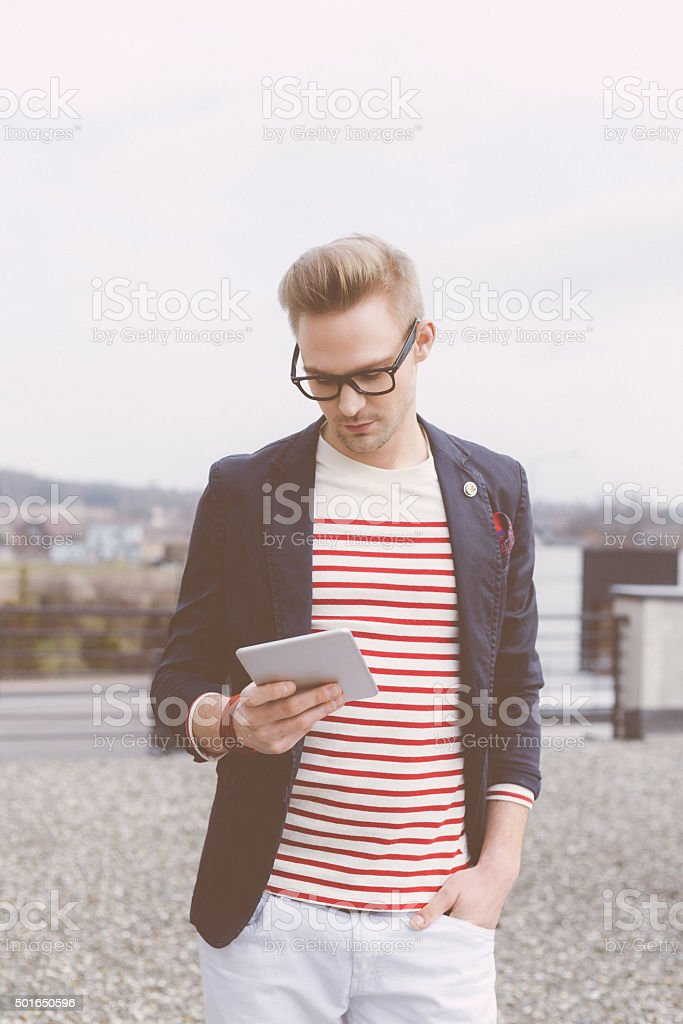 Fashionable blonde young man using a digital tablet outside stock photo