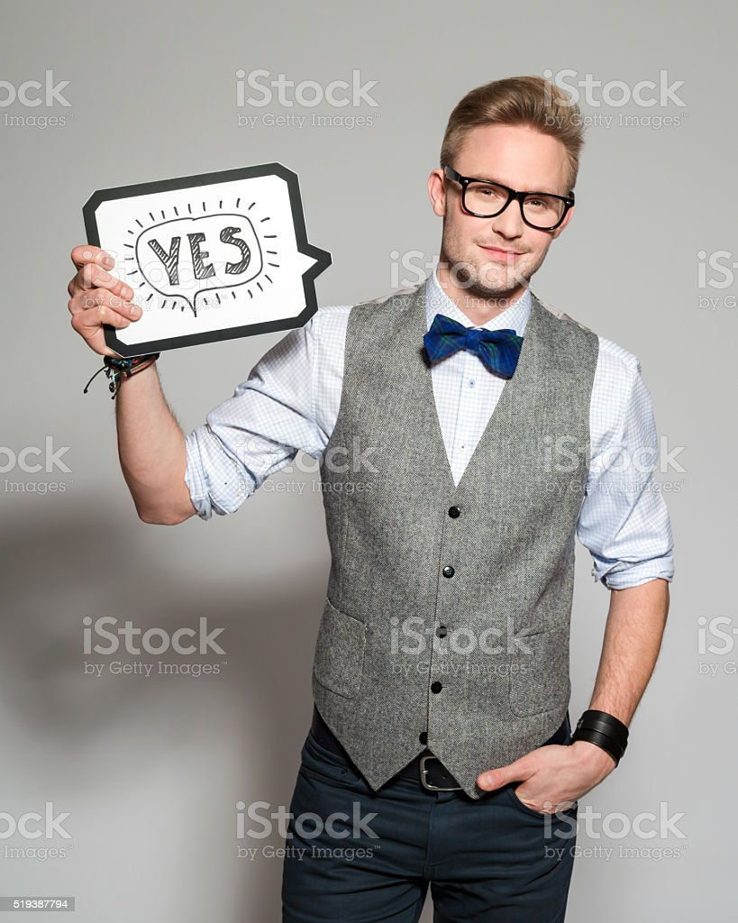 Fashionable blonde young man wearing tweed vest and bow tie stock photo