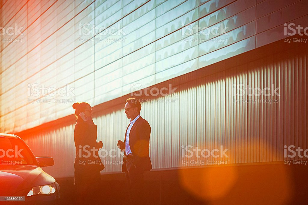 Fashionable business couple in talk at the street beside car stock photo