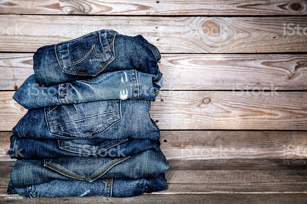 fashionable clothes. pile of jeans on a wooden background stock photo