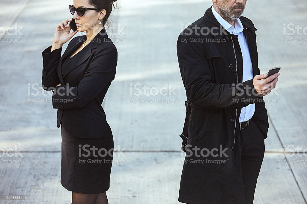 Fashionable couple using mobile phones outdoor. stock photo
