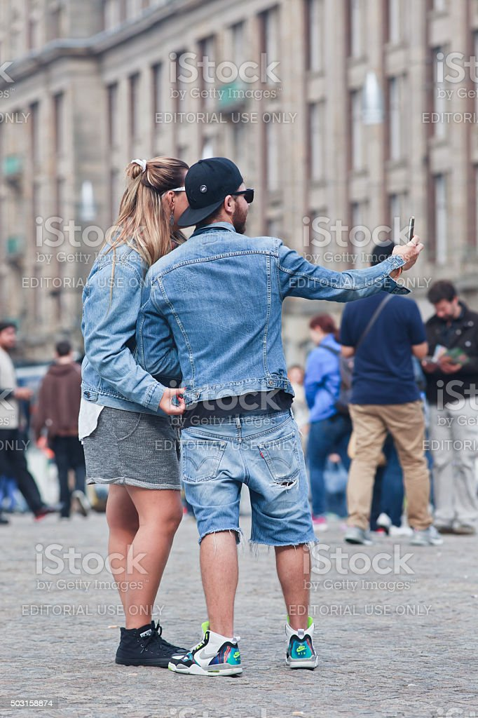 Fashionable dressed Caucasian couple takes selfie on Amsterdam Dam Square stock photo