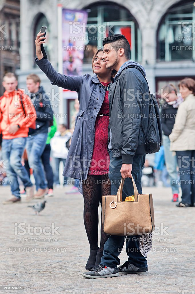 Fashionable dressed cheerful couple takes selfie on Amsterdam Dam Square stock photo