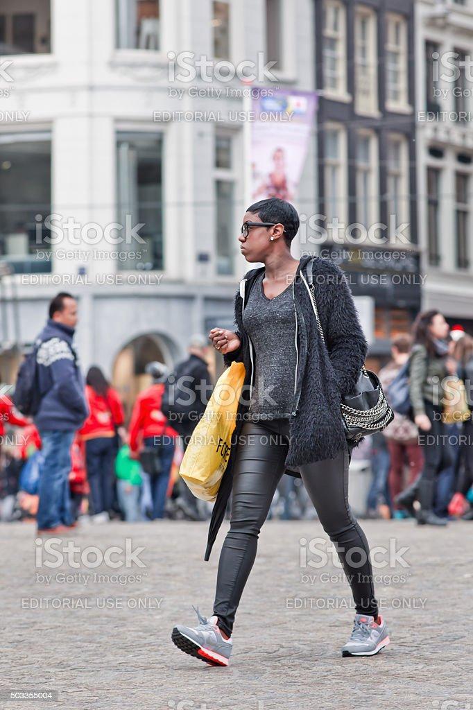 Fashionable dressed Surinam girl walk at Amsterdam Dam Square stock photo