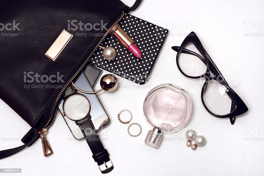 Fashionable female accessories in black bag. Top view stock photo