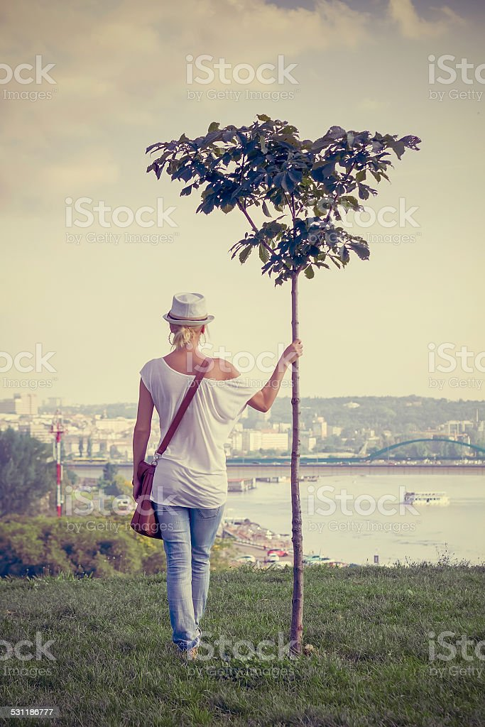 Fashionable girl holding young tree and looking at river stock photo