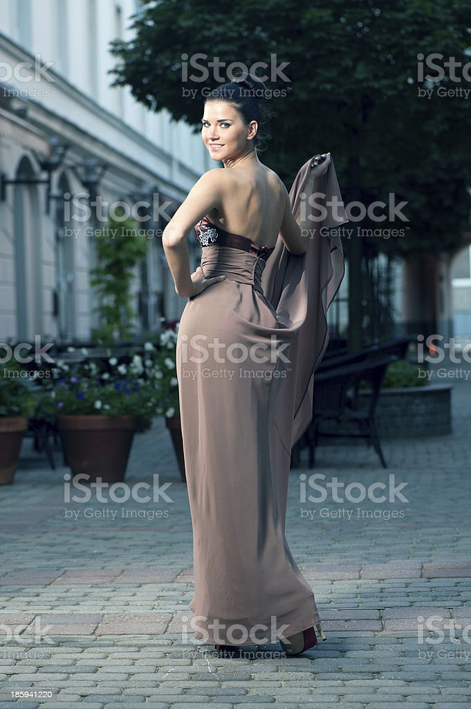 Fashionable girl in brown dress on a city street royalty-free stock photo