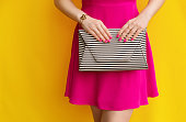 fashionable girl in pink dress with striped handbag