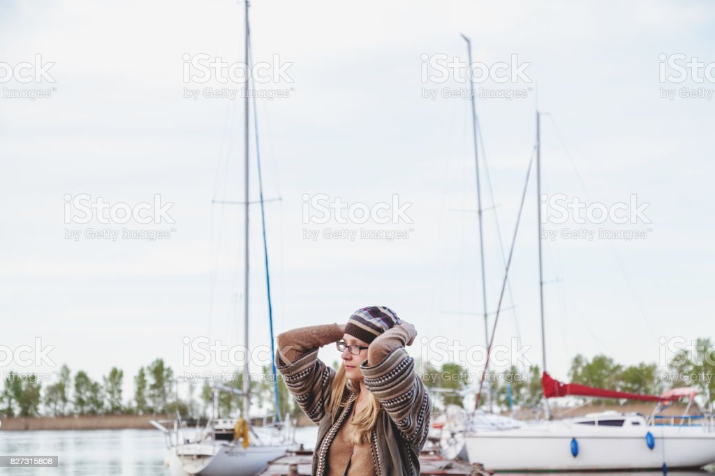 Fashionable girl standing in the eyes against white yacht stock photo