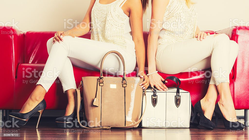 Fashionable girls with bags handbags on red couch stock photo