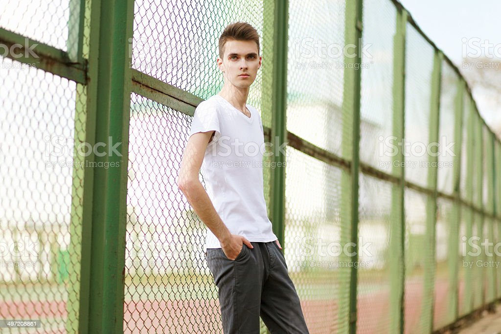Fashionable handsome man model posing outdoors in summer day stock photo