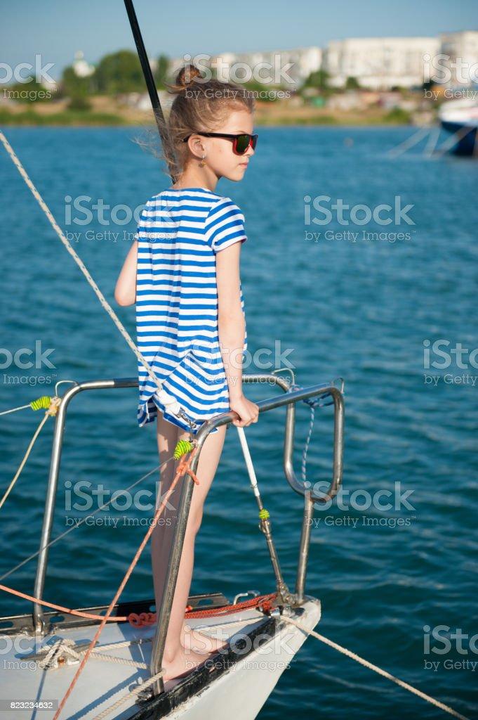 fashionable little girl aboard luxury boat in summer sea cruise