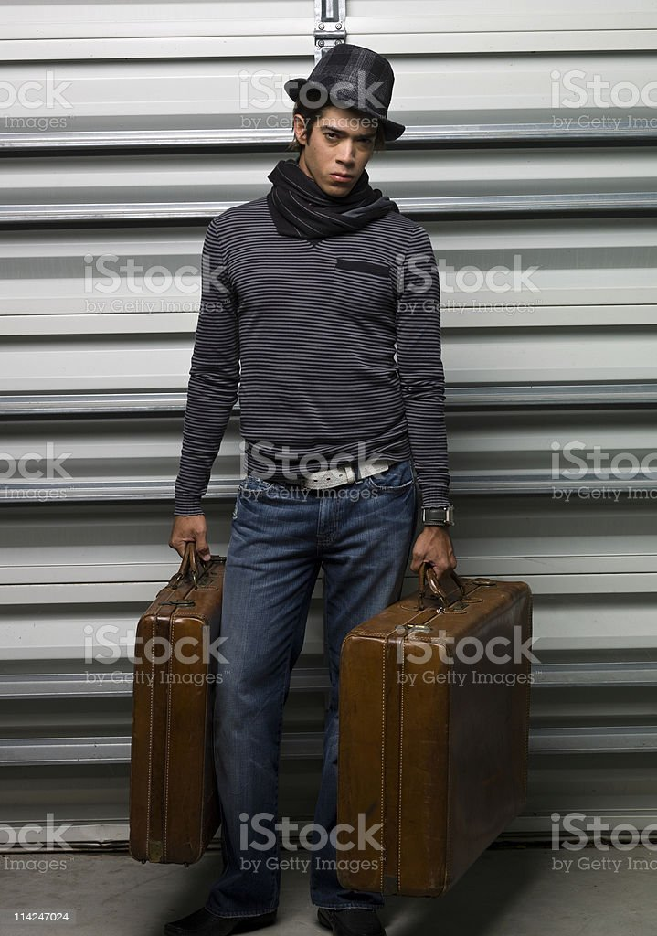 Fashionable Man Holds Two Suitcases, One in Each Hand royalty-free stock photo