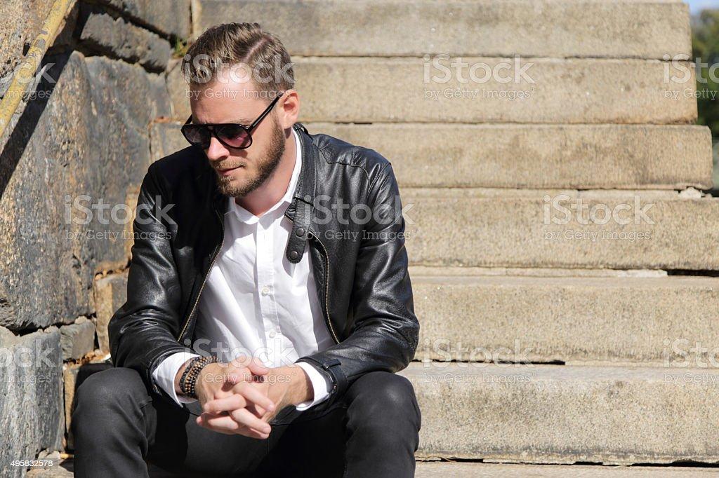 Fashionable man sitting down stock photo