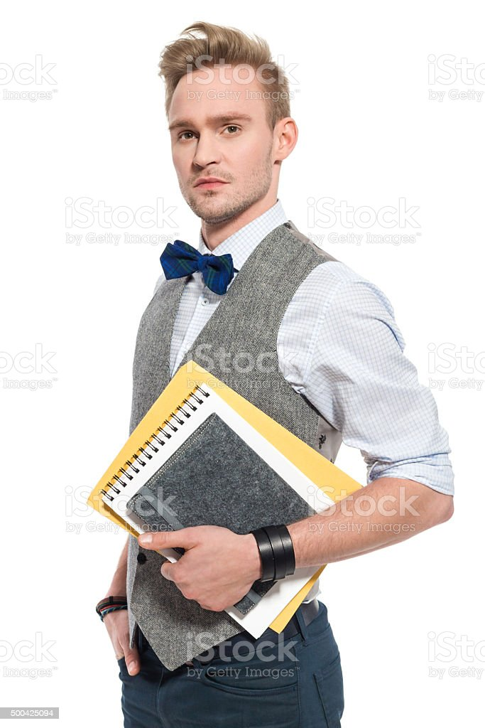 Fashionable man wearing tweed vest, holding notebooks stock photo