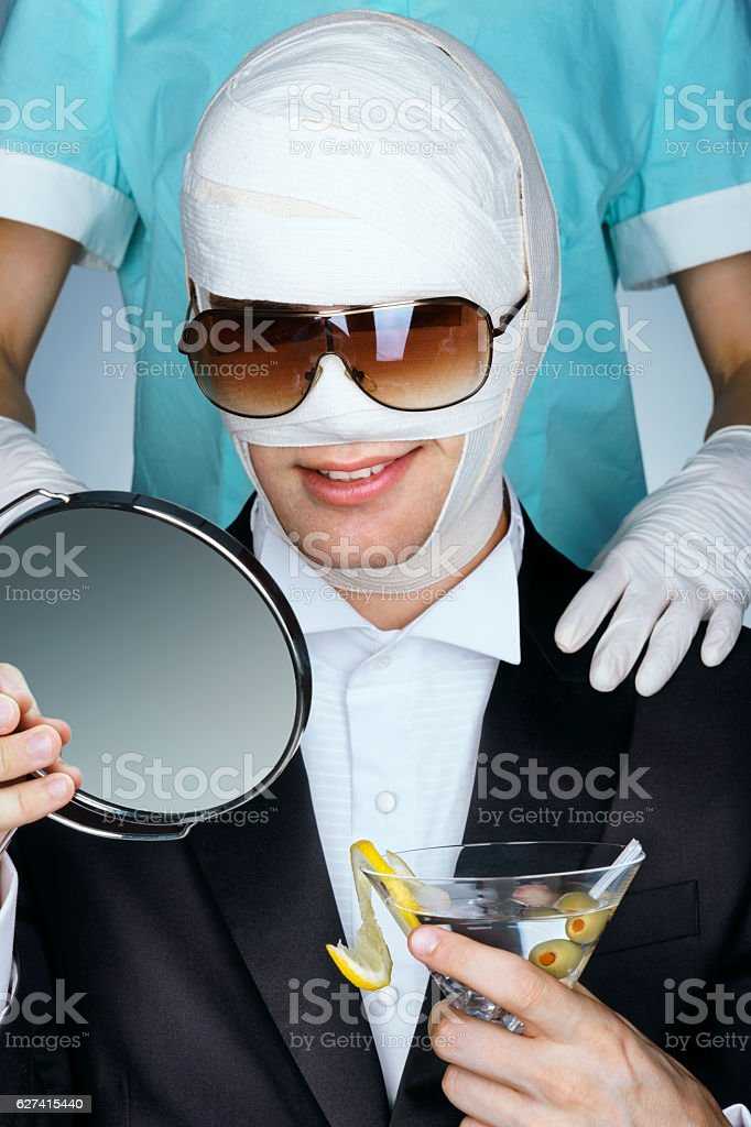 Fashionable man wrapped in medical bandages after facelift stock photo