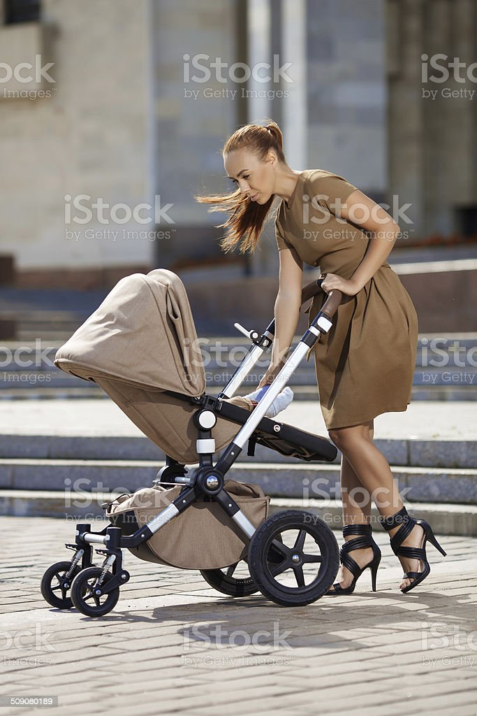 Fashionable modern mother on a urban street with a pram. stock photo