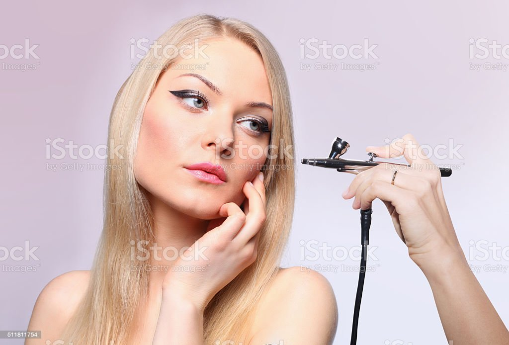 Fashionable portrait of a girl model with hand airbrush. stock photo