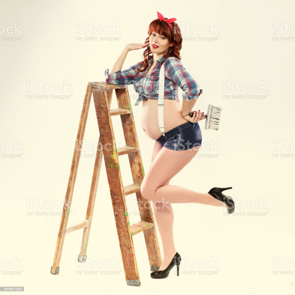 Fashionable redhead pregnant woman painter in pin up style with brush and ladder stock photo