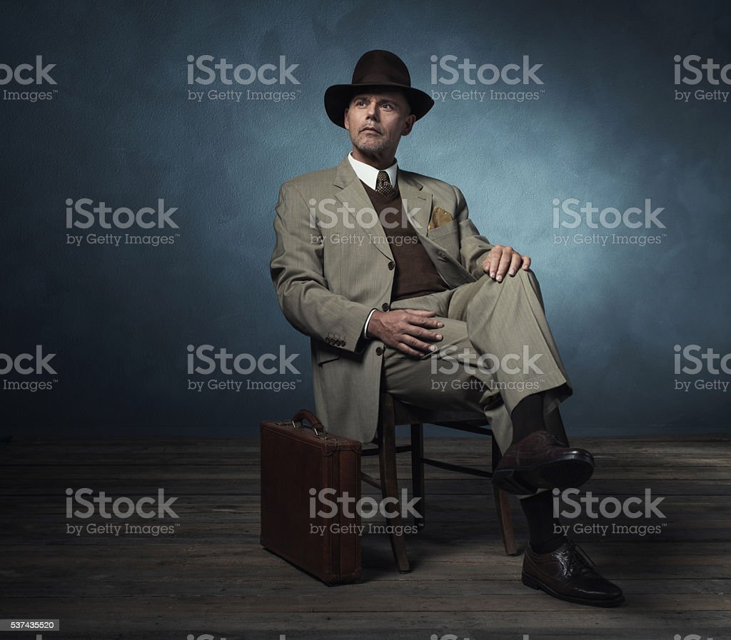 Fashionable retro 1940 business man with hat sitting on chair. stock photo