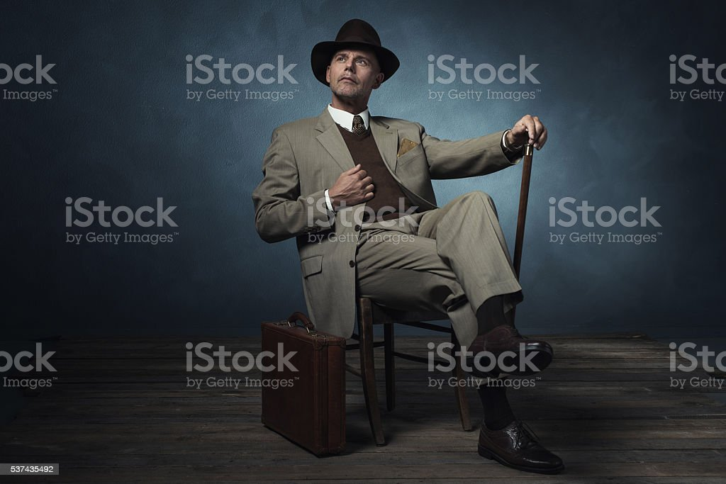 Fashionable vintage 1940 business man with cane sitting on chair. stock photo