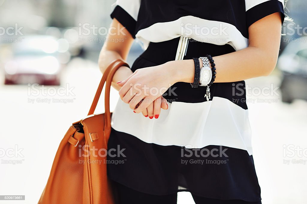 Fashionable woman holding a handbag in hands - close up stock photo