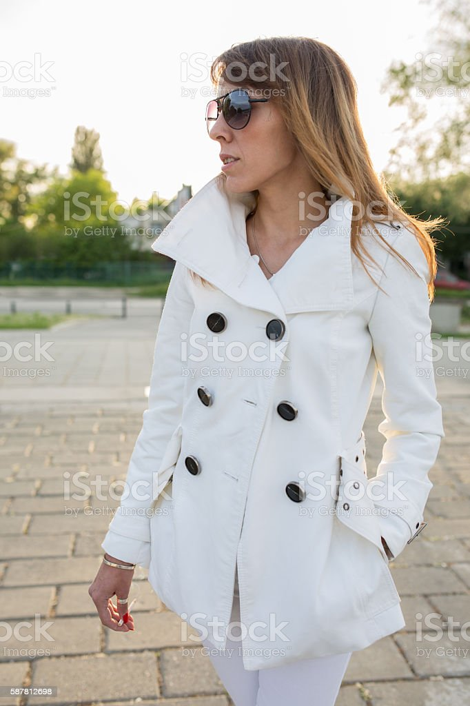 Fashionable woman in a coat standing on the street. stock photo