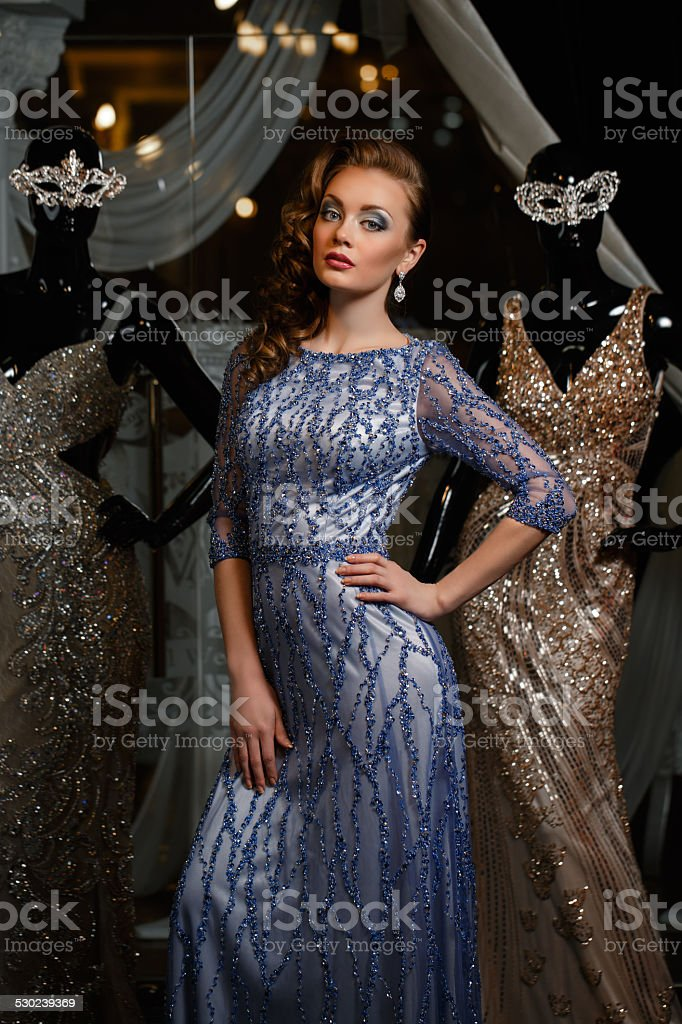 fashionable woman in blue dress with rhinestones and mannequins stock photo