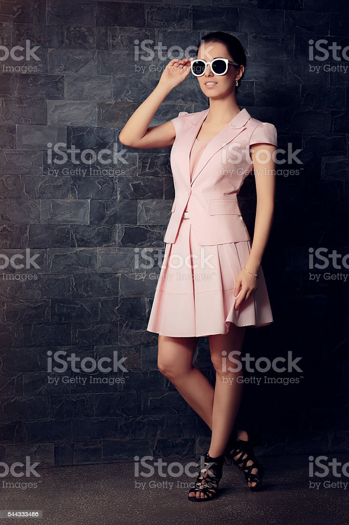Fashionable Woman in Pink Suit with Skirt and Sunglasses stock photo