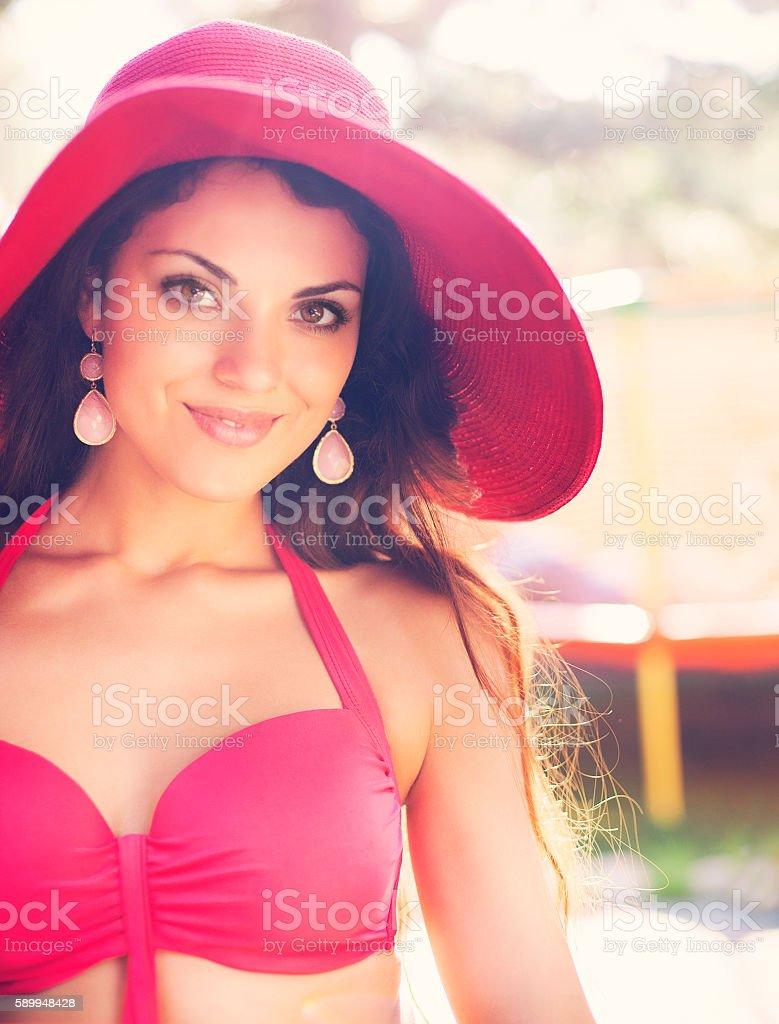 Fashionable woman in red hat posing  bikini stock photo