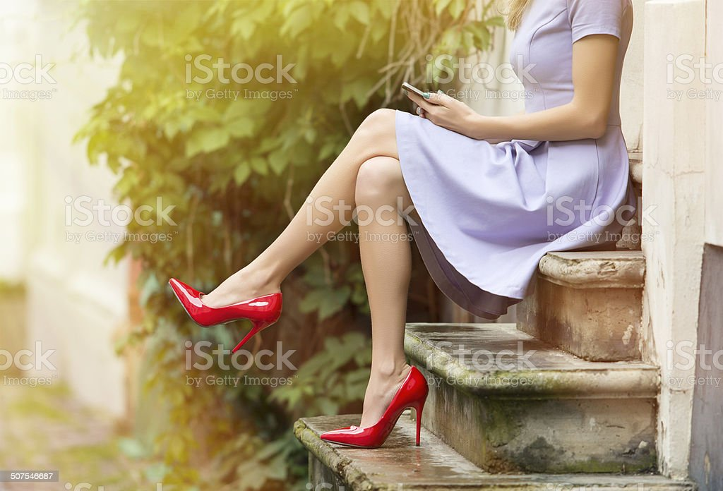 Fashionable woman sitting on stairs stock photo