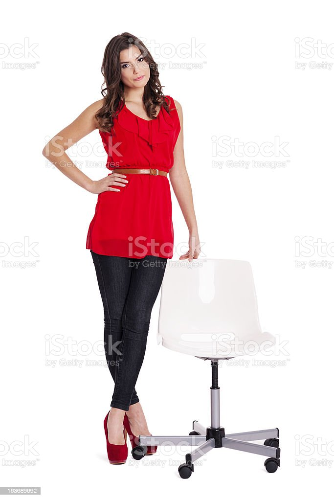 Fashionable woman standing next to a chair royalty-free stock photo