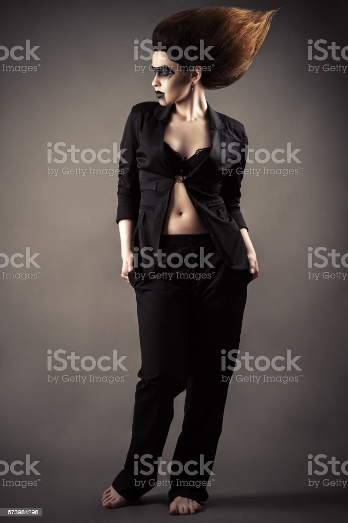 fashionable woman with dark makeup in business suit standing full length stock photo
