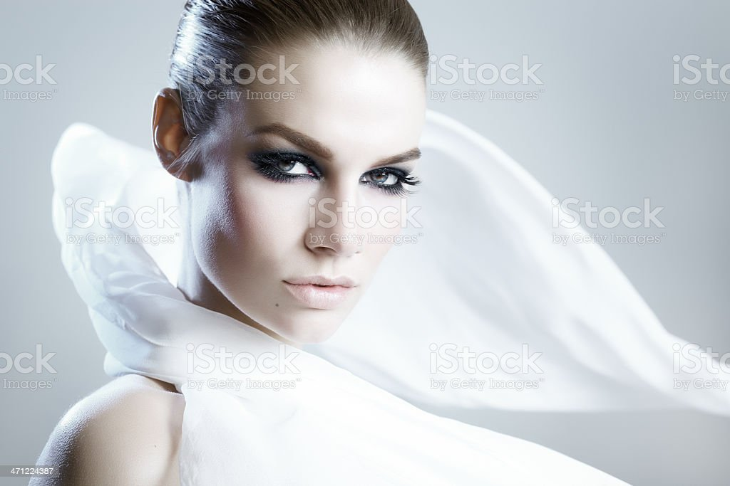 Fashionable woman with white satin cape and dramatic makeup royalty-free stock photo