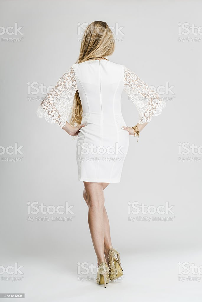 Fashionable woman's elegant sleeved white dress with lace, rear view stock photo
