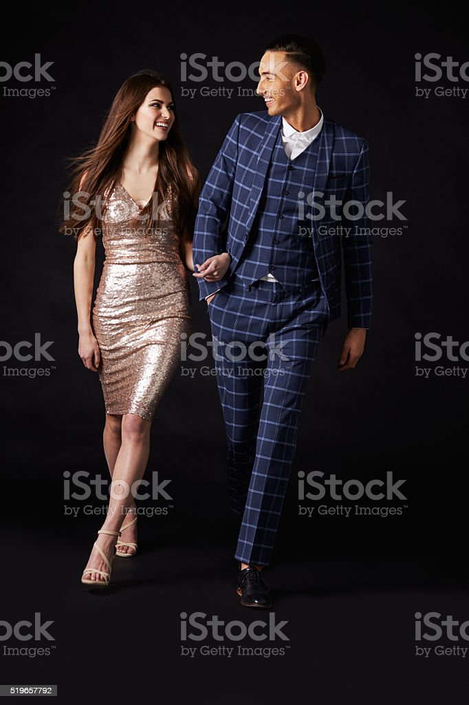 Fashionable young couple walking together arm in arm stock photo