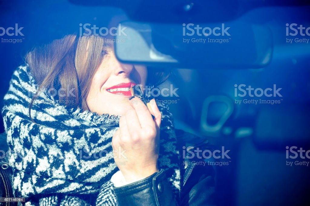 Fashionable young hipster woman  puts on some lipstick. stock photo