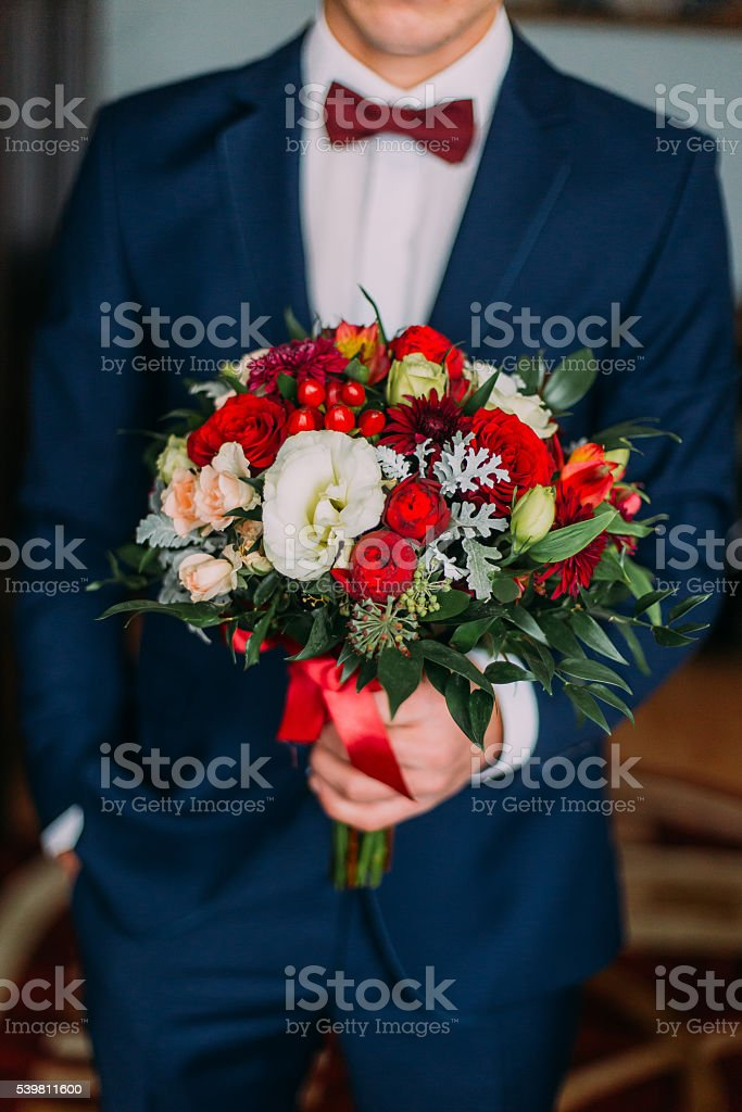 Fashionable young man holding wedding bouquet of red and white stock photo