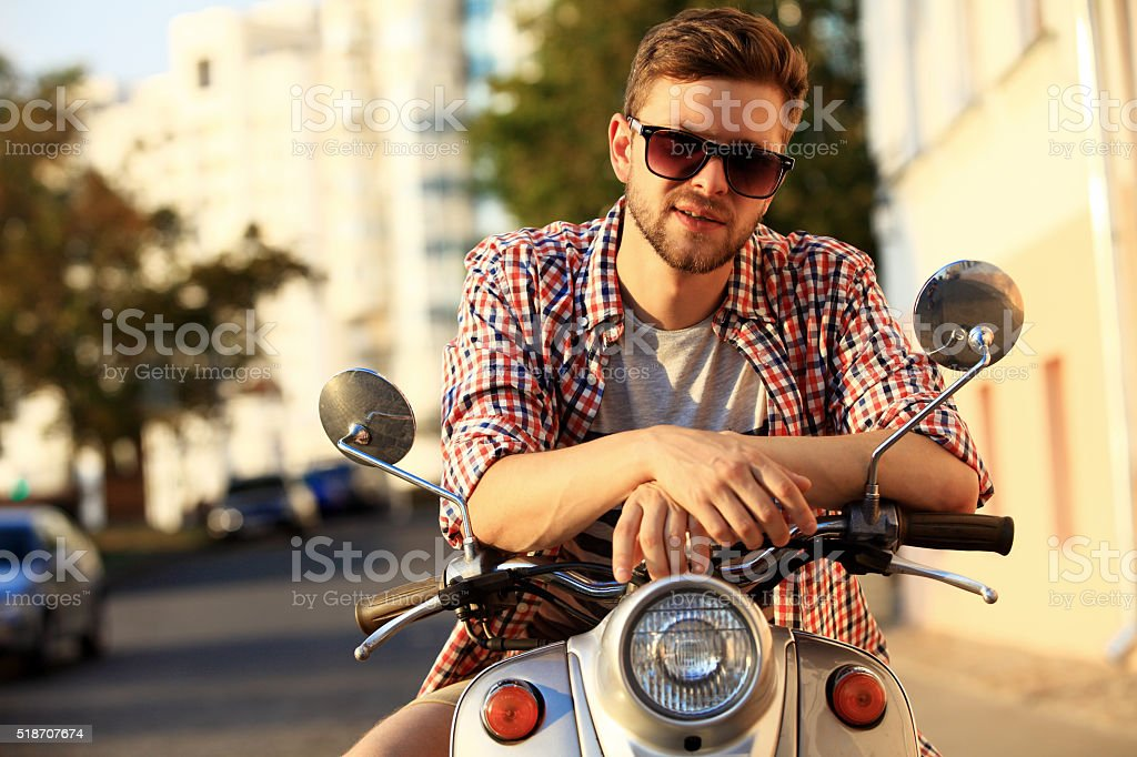 fashionable young man riding a vintage scooter in street stock photo